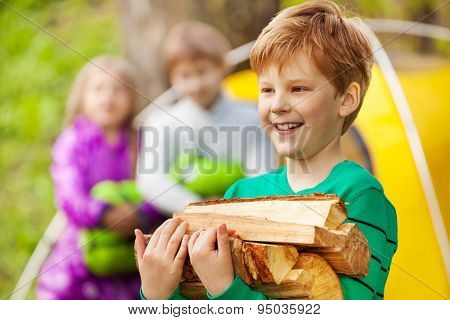 Close-up view of boy holding the wood for bonfire