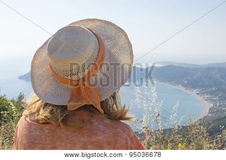 Young Girl With Straw Hat Looking At The Seaside From Extraordinary Viewpoint