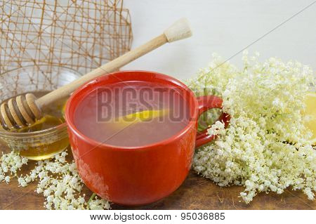 Elderflower Tea With Lemon Served With Bowl Of Honey With A Dipper On  A Table Decorated With Elderf