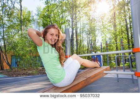 Girl does crunches on the board at sports ground