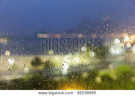 Drops of rain on window with abstract lights out of focus