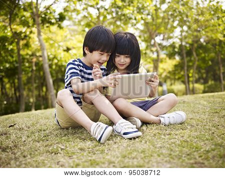 Two Asian Children Using Tablet Outdoors