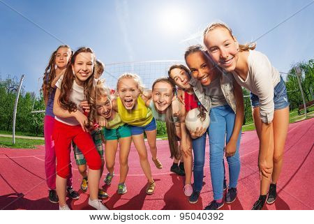 Row of teens standing on the volleyball game court