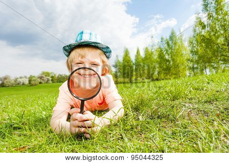 Happy smiling through magnifier boy lays on grass