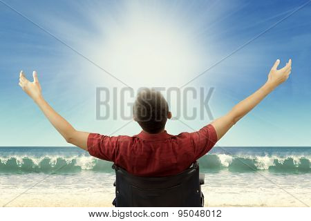 Disabled Man Sitting On Weelchair At Beach