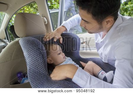 Father Putting His Baby On The Car Seat
