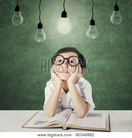 Lovely Child With Book Looking Up At Lamp