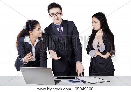 Multiracial Workers Discussing With Laptop Seriously