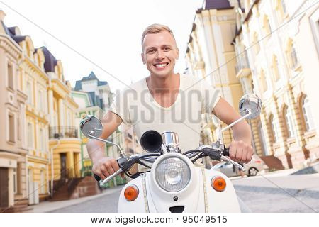 Smiling blond-haired man on scooter