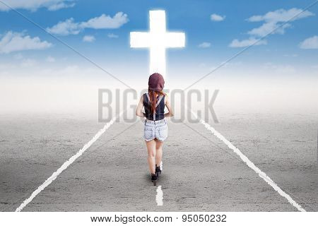 Teenage Girl Walking To The Cross