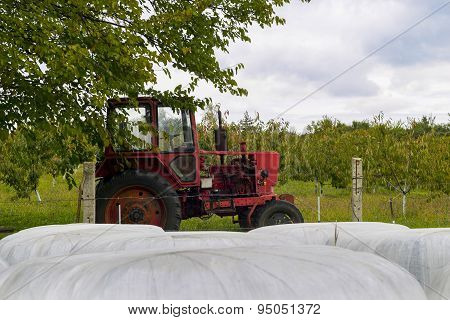 Hay Bales And Old Tractor In Farmfields