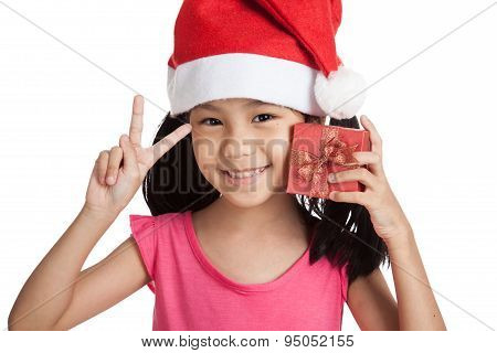 Happy Little Asian Girl Show Victory Sign With Santa Hat And Gift Box