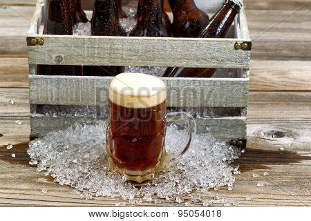 Cold Dark Beer In Large Glass Mug With Vintage Crate With Ice Cold Bottled Beer On Rustic Wooden Boa