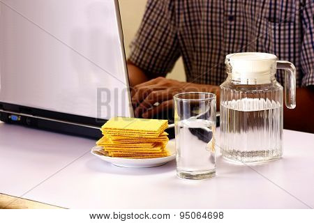 Glass and pitcher of water and a stack of crackers and man working on a laptop computer in the backg