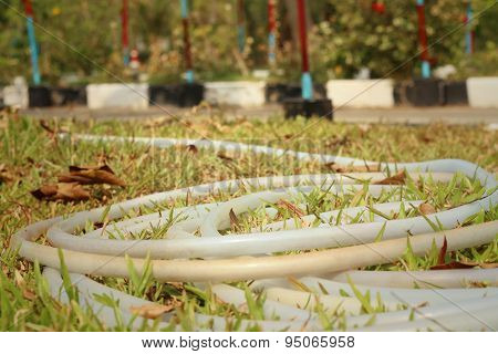 Rubber Tube For Watering Plants On Green Grass.