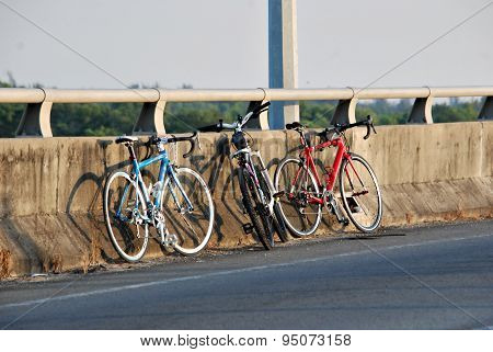 Three Bicycles Parked Against Wall By The Roadside On A Sunny Morning.