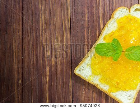 bread and orange jam on wooden table