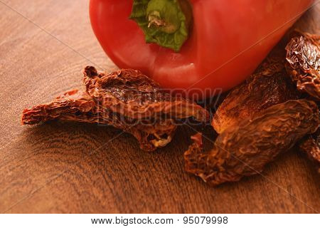 Sun Dried Tomatoes And A Red Pepper On A Cutting Board