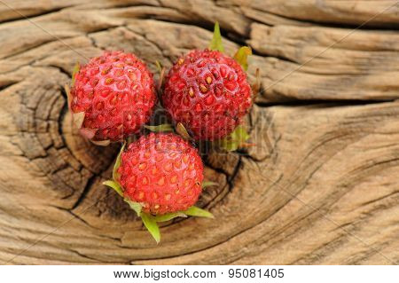 Three Wild Strawberries Fragaria Viridis On Cracked Wooden Board