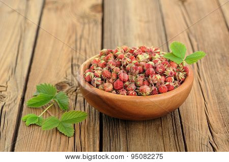 Wild Strawberries Fragaria Viridis With Green Leaves In Wooden Bowl On Rustic Wooden Table