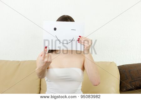 Girl Holds Forefinger And Smiley Drown On Paper.