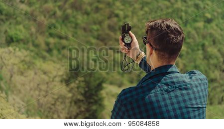 Hiker Man Searching Direction With A Compass Outdoor