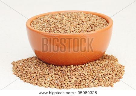 Buckwheat In Brown Ceramic Bowl On A White Fabric.