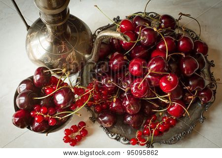 Cherry With Red Currants In A Bowl And A Metal Plate In Oriental Style .