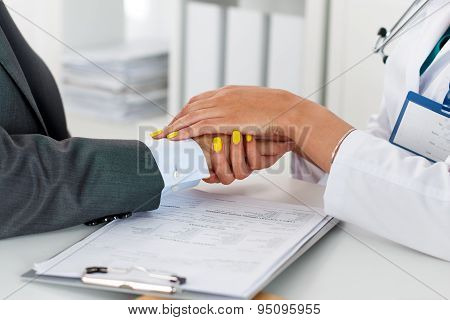 Friendly Female Doctor's Hands Holding Male Patient's Hand