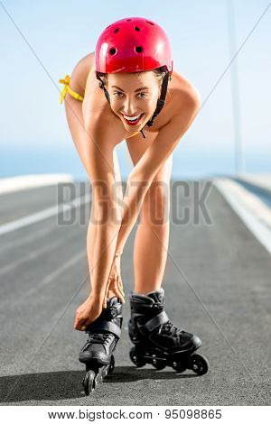 Woman in swimsuit with rollers on the highway