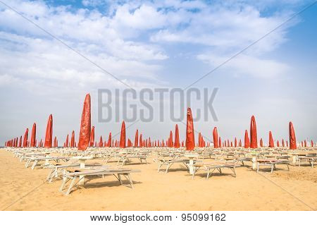 Red Umbrellas And Sunbeds At Rimini Beach - Italian Summer Overview At The Beginning Of The Season