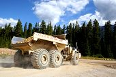 image of dump_truck  - a giant dump truck hauling rocks during road construction in a forested area - JPG