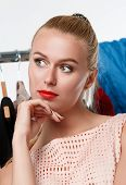 picture of wearing dress  - Beautiful blonde woman suffering near wardrobe rack full of clothes choosing dress to wear - JPG