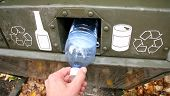foto of recycling bin  - a person deposits a plastic water bottle into a green recycle bin - JPG