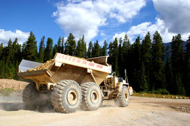 stock photo of dump_truck  - a giant dump truck hauling rocks during road construction in a forested area - JPG