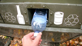 picture of recycle bin  - a person deposits a plastic water bottle into a green recycle bin - JPG