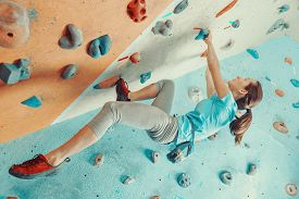 pic of climb up  - Sporty young woman training in a colorful climbing gym - JPG