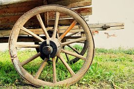 stock photo of yesteryear  - Wheel of old wooden cart taken closeup - JPG