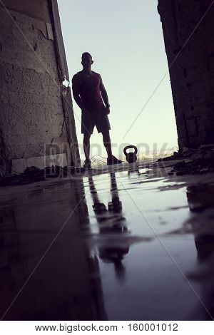 Reflection of a muscular athletic built young athlete working out with a kettlebell in a ruin building next to a puddle of water