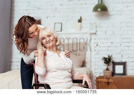 My dear. Pleasant elderly woman smiling and sitting in the wheelchair while her loving granddaughter taking care of her