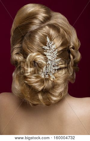 Beautiful blond girl with perfect skin, evening make-up, wedding hairstyle and accessories. Hairstyle back View. Picture taken in the studio.