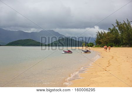 beautiful views of the sea and beach of Vietnam, transparent clear water, a wide Golden beach, lots of greenery and umbrellas with thatched roof, on the horizon, the hills, the dull sky with clouds and two water motorcycle, hydrometer