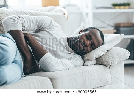 Feeling stomachache. Handsome young African man keeping eyes closed while lying on the sofa and touching his stomach