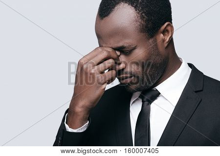 Stressed and tired. Young African man in formalwear massaging nose and keeping eyes closed while standing against grey background