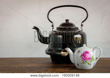 Large metallic teapot and little ceramic teapot