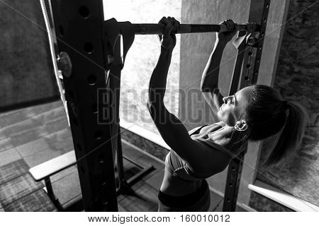 Importance of sport. Hard working good looking persistent woman doing chin ups and focusing on this physical activity while holding a horizontal bar