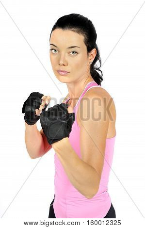 Attractive fitness woman in an aggressive pose with clenched fists. Studio white background