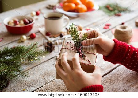 Hands of unrecognizable woman wrapping and decorating Christmas present against wooden table background. Studio shot.