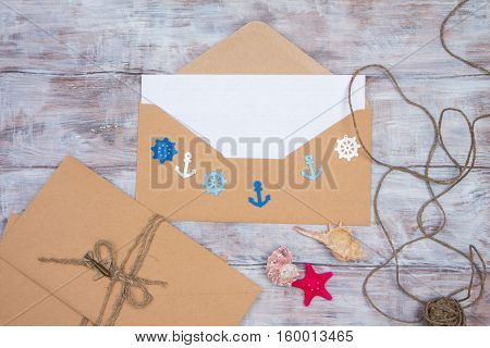 Envelope with blank sheet of paper and embellishments in nautical theme - steering wheel anchors shells and starfish. Space for your text
