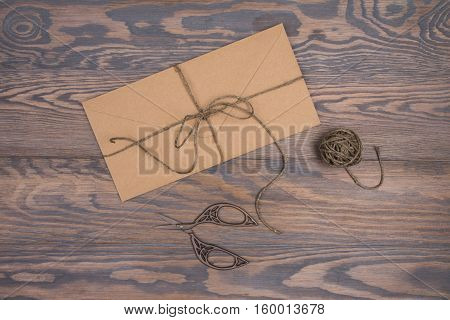 Kraft envelope tied with twine and vintage scissors on a wooden brown background